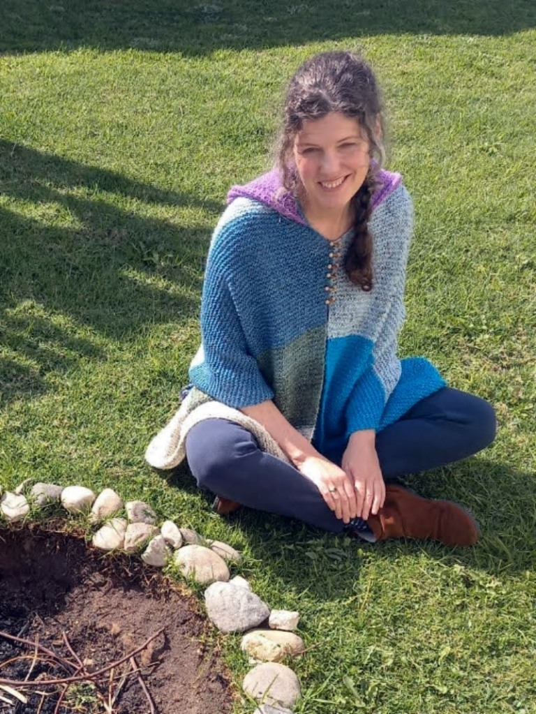 Photograph of Michele Damstra sitting on a lawn, wearing her knitted poncho